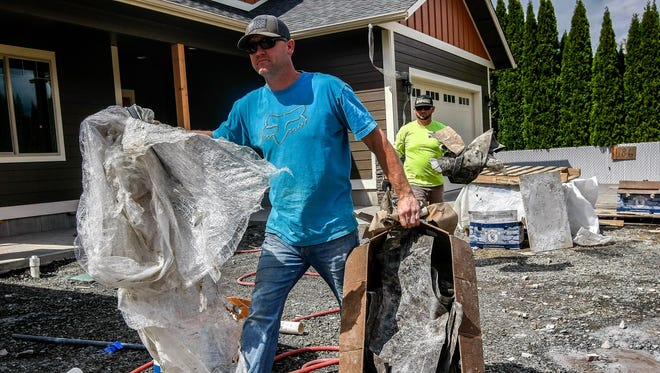Leon Roberson of Leon Roberson Construction, left, and Cody Ferrano, haul debris from two spec homes near completion at the end of Primrose Lane in Roseburg, Ore.