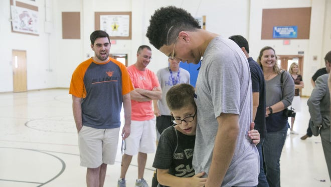 Noah Smith, 11, hugs Devin Booker after finding out he will be joining Booker traveling to New York for the NBA draft lottery at Navarrete Elementary School in Chandler, Ariz. on May 12, 2017.