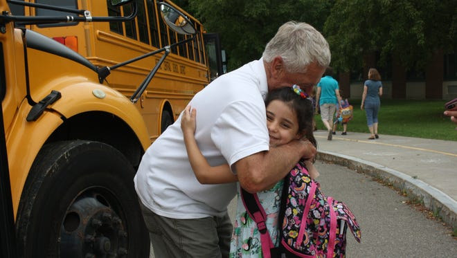 Neveah Bartra, 6, of Apalachin, hugs Bob Breed before his last route.