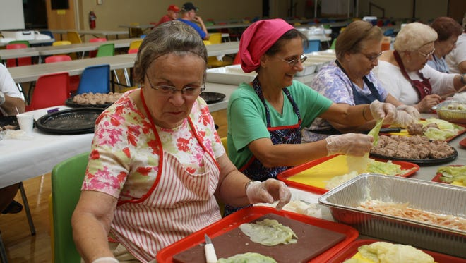An assembly line of about 30 people prepare halupki for St. Cyril's Parish Festival on Wednesday.