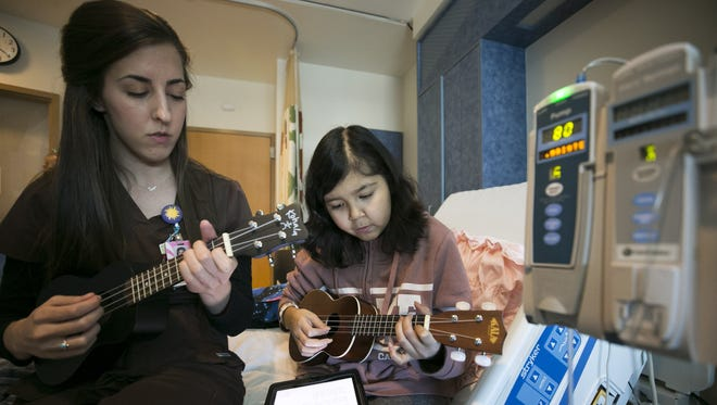 "Kaylee Moreno, 14, of San Tan Valley, who has leukemia and pediatric music therapist Olivia Houck perform Elvis' ""Can't Help Falling In Love"" on their ukuleles at Cardon Children's Medical Center in Mesa on March 20, 2018. Kaylee learned to play the ukulele though the music therapy program at CardonÊChildren'sÊMedical Center during one of her stays at the hospital since being diagnosed with leukemia in 2015."