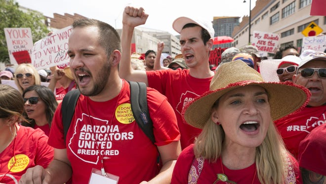 Dylan Wegela (left) Noah Karvelis, both teachers and leaders with Arizona Educators United, and Catherine Barrett, an English teacher at Carl Hayden High School, march from Chase Field in downtown Phoenix to the Arizona capitol on the first day of the teacher walkout on April 26, 2018.