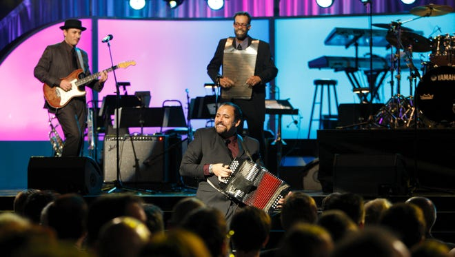 Ralph Fontenot, pictured playing the rubboard in the back of this photo from the 50th Annual Grammy Awards show with  Terrance Simien and the Zydeco Experience, died Wednesday while on tour.