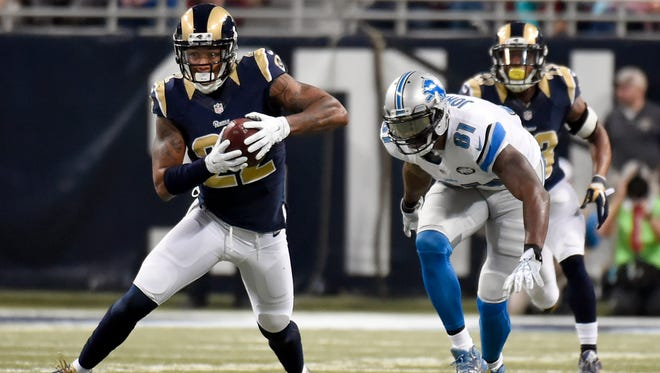 St. Louis Rams cornerback Trumaine Johnson, left, intercepts a pass intended for Detroit Lions wide receiver Calvin Johnson, right, before running the ball back for a touchdown during the second quarter of an NFL football game Sunday, Dec. 13, 2015, in St. Louis.