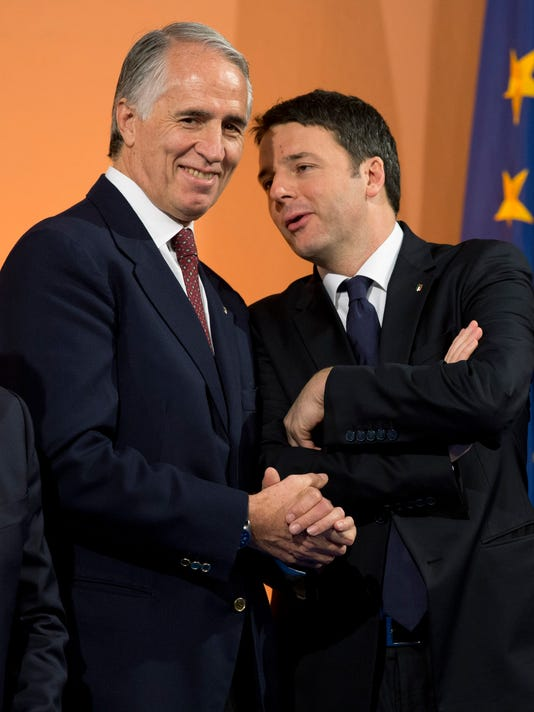 """Italian Premier Matteo Renzi, right, talks with CONI, Italian Olympic Committee, President Giovanni Malago' at Italian Olympic Committee headquarters in Rome, Monday, Dec. 15, 2014. Renzi says Rome will bid for the 2024 Summer Olympics. He says """"the Italian government, together with CONI, is ready for this project."""" The move comes with Italy's economy still stagnant and amid a widening corruption and mafia scandal in the capital. Italy planned to bid for the 2020 Olympics but the project was scrapped after then-premier Mario Monti refused to provide financial backing. The 2024 host will be chosen in 2017. (AP Photo/Andrew Medichini)"""