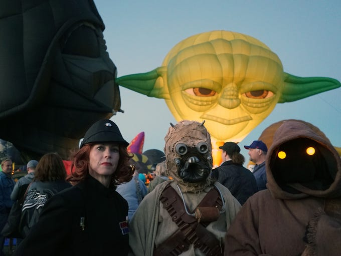 Three people dressed in Star Wars costumes stand before