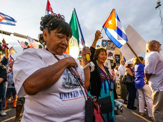 A woman holds her heart during the US National Anthem. The Bay of Pigs Veterans Association held a rally in Little Havana for Cuban freedom. These older Cuban exiles are dwindling, while the younger generation of Cubans are more lenient toward the Castro regime.
