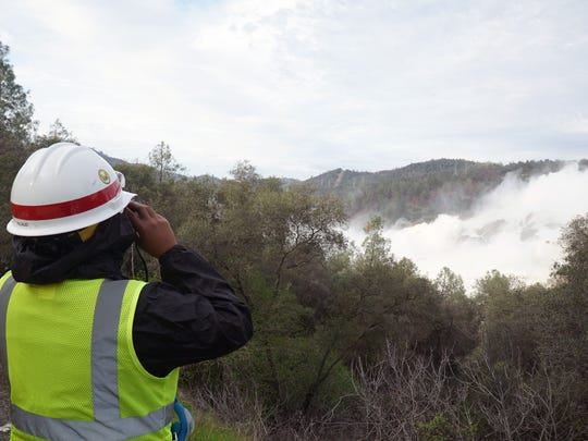 An engineer with the U.S. Army Corps of Engineers monitors water spilling from the Oroville Dam. The dam is controlled by the California Division of Water Resources, but the Army Corps of Engineers was providing assistance in monitoring and developing repair plans.