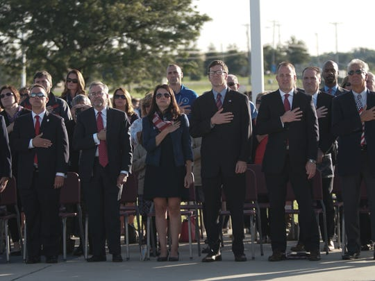 Members of the community and school leaders stand at attention during a memorial service honoring the men and women who lost their lives at the World Trade Center in New York City, the Pentagon in Washington, D.C., and on U.S. Air Flight 93 in Shanksville, Pennsylvania, on Sept. 11, 2001.