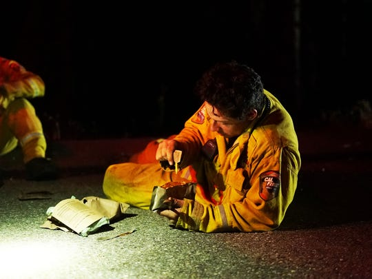 Seasonal CalFire firefighter Derek Longoria stops for a dinner break just after midnight on July 31, 2018, while fighting the Carr Fire near Redding, Calif. Longoria is reclining on the pavement of a road, which is also acting as a fire break to slow the spread of the blaze.