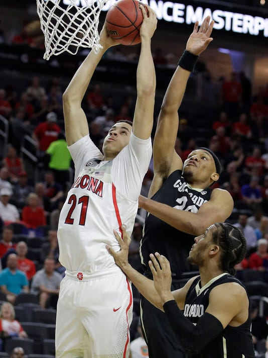 Arizona's Chance Comanche (21) dunks in front of Colorado's George King during the first half of an NCAA college basketball game in the quarterfinals of the Pac-12 men's tournament Thursday, March 9, 2017, in Las Vegas. (AP Photo/John Locher)