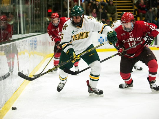University of Vermont defenseman Yvan Pattyn, left, battles for the puck during a college men's hockey game against St. Lawrence last season.