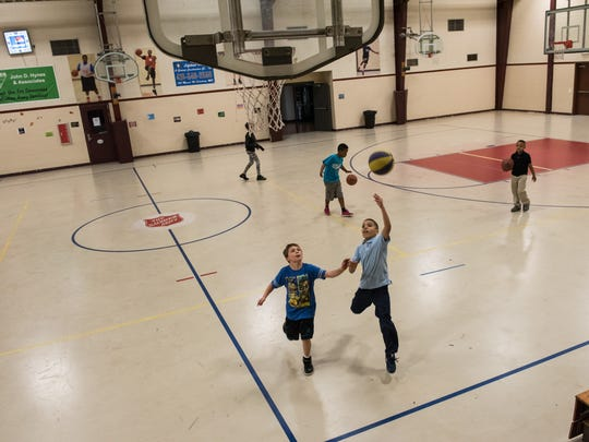Children play basketball at the Salvation Army Youth Club gymnasium.