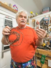 Artist Greg Saunders explains the use of common items like barbed wire that he uses for his sculptures at his studio in Pensacola on Friday, May 26, 2017.