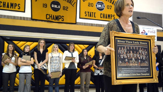 River View coach Carolyn Daugherty holds up a picture of the 2007 River View state champion team after they were inducted into the River View High School Hall of Fame.