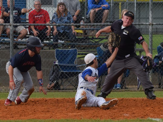 The umpire calls an out against North Vermillion's Dylan Duhon (14, far left) after Buckeye pitcher Isaac Smith (12, front center) shows the umpire the ball after he tagged Duhon out at home plate in a playoff game played Monday.