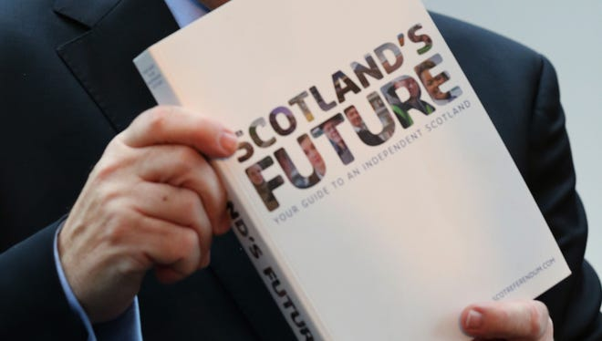 Scotland's First Minister Alex Salmond  holds a copy of the government's  blueprint for independence.