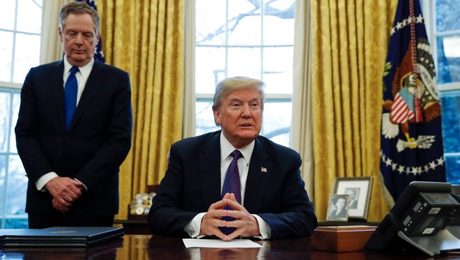 "President Trump, joined by U.S. Trade Representative Robert Lighthizer, waits for reporters to take their places before signing Section 201 actions in the Oval Office Tuesday. Trump says he is imposing new tariffs to ""protect American jobs and American workers."" Trump acted to impose new tariffs on imported solar-energy components and large washing machines in a bid to help U.S. manufacturers."