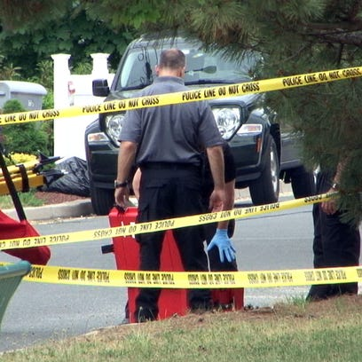 Investigators gather equipment outside 33 Bayview Parkway