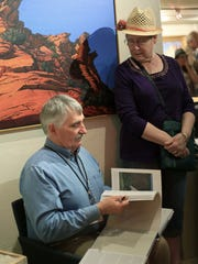 Royden Card talks with art enthusiasts during a book