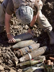 A U.S. Army bomb team member disposes of artillery used by insurgents in Afghanistan to make improvised explosive devices.