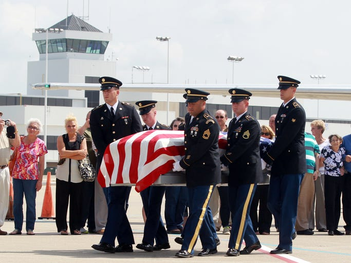 A Honor Guard carries past his family a casket bearing the remains of  Sgt. Paul M. Gordon, of Crittenden, who died in a prisoner of war camp in 1951 during the Korean War.