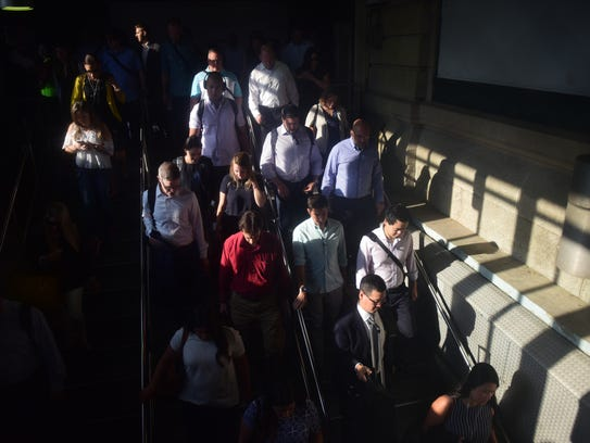 Commuters head down the stairs to the PATH as they