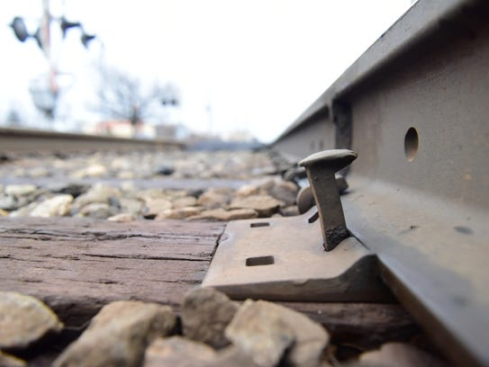 A railroad spike partially lifted off the tracks, near