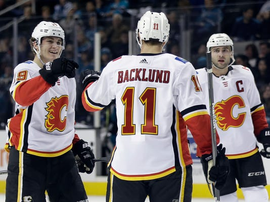 Calgary Flames' Mikael Backlund (11) celebrates his goal with teammates Matthew Tkachuk, left, and Mark Giordano during the first period of an NHL hockey game against the San Jose Sharks on Thursday, Dec. 28, 2017, in San Jose, Calif. (AP Photo/Marcio Jose Sanchez)