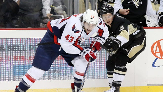 Washington Capitals right wing Tom Wilson (43) and Pittsburgh Penguins defenseman Olli Maatta (3) battle for the puck during the third period at the CONSOL Energy Center.
