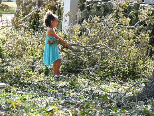 Amira Johnson 6, was one of the kids who began to chip in when the Daniels family started cleaning. Kids and adults teamed up to clean up Hurricane Irma branch and leaves debris carpeting the playground area of Taylor Park in Cocoa Village.