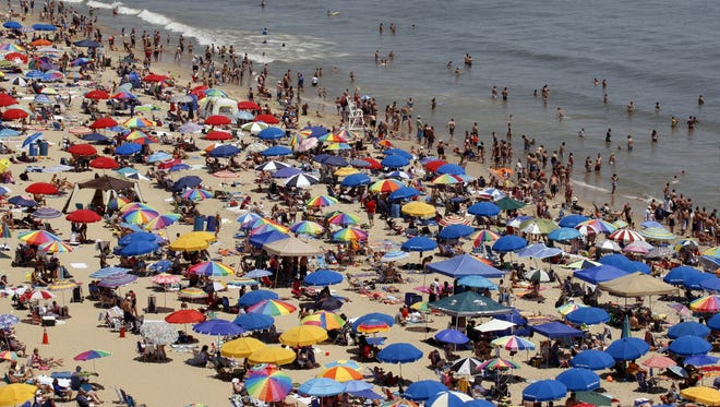 In this June 9, 2012, photo, people crowd the beach in Ocean City, Md. Beginning May 1, 2015, smoking and vaping will only be allowed at the back of the beach or within 15 feet of a boardwalk ashtray.