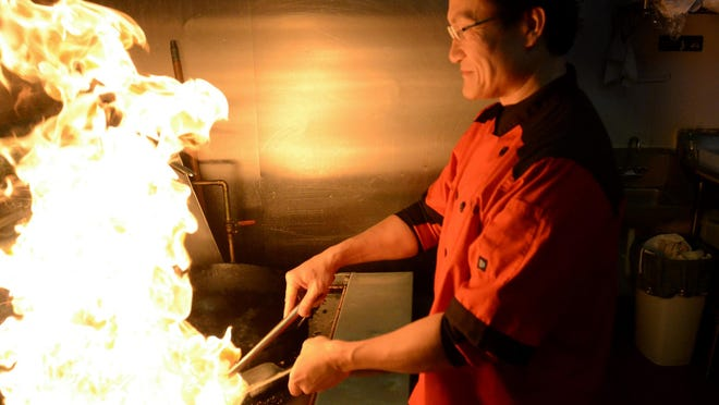 Chef Tom Lin heats things up in the kitchen in his Commerce Township eatery Szechuan Empire. Lin will be helping to teach a sushi-making class at the YMCA.