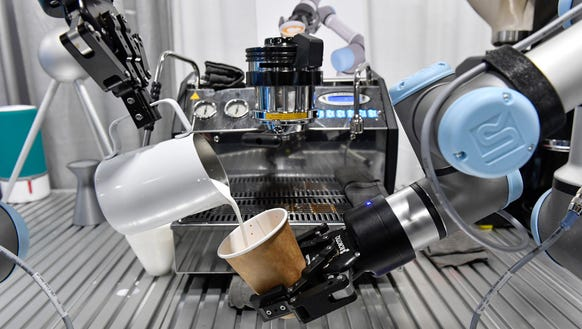 A robot barista makes a cup of coffee during the opening