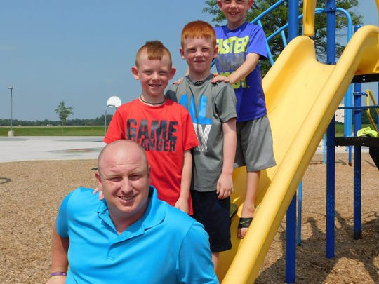 Adam Greenslade poses for a photo with sons, Joel, Sam and Aiden, on the slide at the school playground.