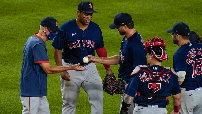 Red Sox opener Colten Brewer hands the ball to manager Ron Roenicke, left, as he leaves during the third inning Friday night at Yankee Stadium.
