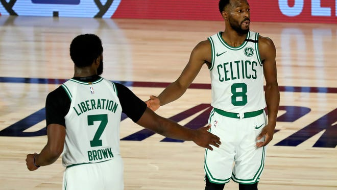 Celtics guard Jaylen Brown, left, teammate Kemba Walker celebrate during the second half against the Philadelphia 76ers in Game 3 of a first-round playoff series Friday in Lake Buena Vista, Fla.