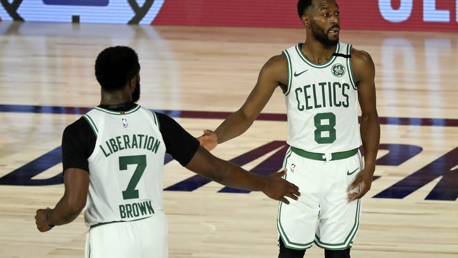 Boston Celtics guard Jaylen Brown (7) and Boston Celtics guard Kemba Walker (8) celebrate during the second half against the Philadelphia 76ers in Game 3 of an NBA basketball first-round playoff series, Friday, Aug. 21, 2020, in Lake Buena Vista, Fla.