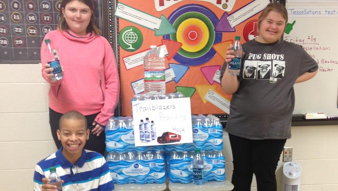 Camp Ernst Middle School students Brianna Carr, Kobe Turner and Ashley Lightner are encouraging the school to bring bottled water and notes of encouragement to send to Flint, Michigan.