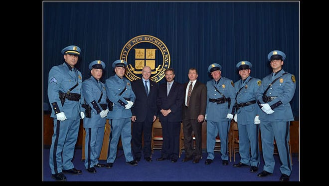 Six promoted New Rochelle police officers with New Rochelle leaders  at the promotion ceremony April 17, 2014, in City Hall. From left: New Sgt. Adam Castiglia, new Detectives Frank Lore and Aaron Goldstein, Police Commissioner Patrick J. Carroll, City Manager Charles B. Strome III, Deputy Commissioner Anthony Murphy, and new Detectives Richard Gargan,  John Hansen and Dario Navarrete.