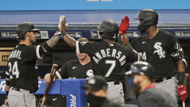 Chicago White Sox's Tim Anderson (7) is congratulated by teammates after scoring in the ninth inning in a baseball game against the Cleveland Indians, Wednesday, July 29, 2020, in Cleveland.