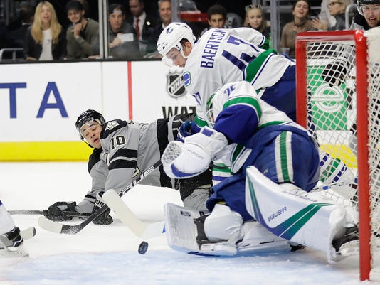 Los Angeles Kings' Devin Setoguchi (10) has his shot stopped by Vancouver Canucks goalie Jacob Markstrom, foreground, of Sweden, during the second period of an NHL hockey game Saturday, Oct. 22, 2016, in Los Angeles. (AP Photo/Jae C. Hong)