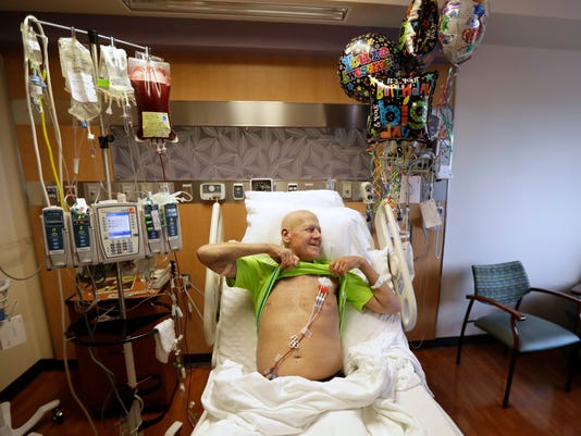 CORRECTS FROM MD ANDERSON HOSPITAL TO MD ANDERSON CANCER CENTER- Sportscaster Craig Sager holds up his shirt as his wife Stacy takes a picture after starting his transplant procedure Wednesday, Aug. 31, 2016, at MD Anderson Cancer Center in Houston. Sager underwent his third bone marrow transplant as he continues to battle Acute myeloid leukemia. (AP Photo/David J. Phillip)
