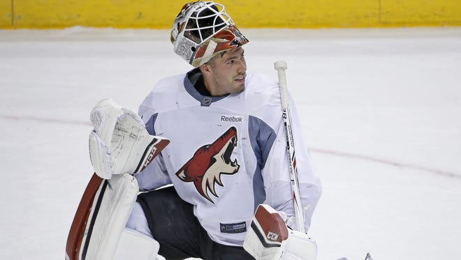 Coyotes goalie Louis Domingue talks with coaches during a practice at Gila River Arena on September 25, 2016 in Glendale.