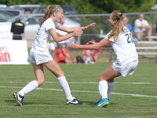 Novi's Avery Fenchel (left) is congratulated by teammate Julia Stadtherr after scoring the only goal giving Novi a 1-0 victory over Grand Blamc to claim the Div. 1 state soccer title June 15 at Williamston High School.