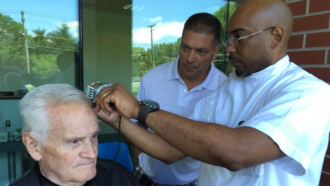 Joe Kilgallen gets a haircut by Anthony Barton while student Gino Morasco looks on at Greenburgh Town Hall.