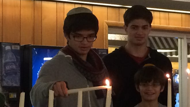Nathan Abramoff, 16, left, lights a menorah made of bowling pins. Next to him are his brothers Boaz Abramoff, 11, front, and Yair Abramoff, 17, back.