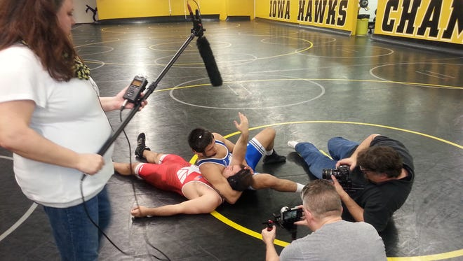 Carrie Miell, left, and Kory Cousins, with his back to the camera, of OnMedia Cable TV production film the Unviersity of Iowa College of Dentistry's Super Bowl commercial. On the mat are wrestler Tony Ramos, blue singlet, and Nick Kanellis, an actor wearing the red singlet.