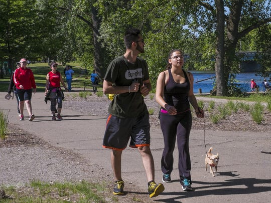 Halwest Saeid and Ambrosia Pearsall walk along the Lansing River Trail with their dog Chacha Chia as part of the Mayor's Family River Walk.