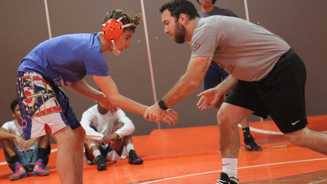 First-year Tyger coach Zach Brumfield drills with unbeaten Josh Lyons in preparation for this weekend's 56th J.C. Gorman Invitational at Mansfield Senior.